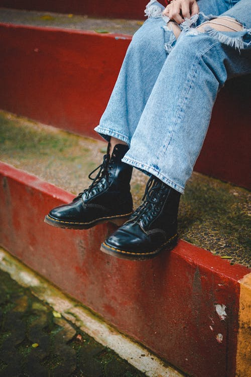 A Person Wearing Ripped Denim Jeans and Black Leather Boots