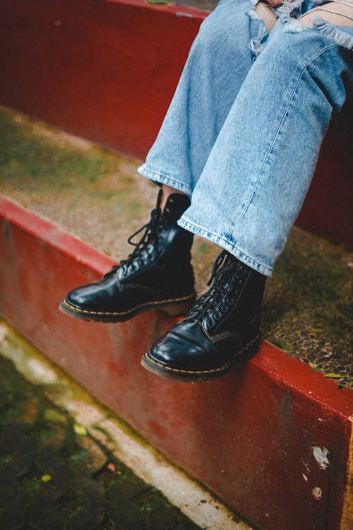 A Person in Ripped Denim Jeans and Black Leather Boots