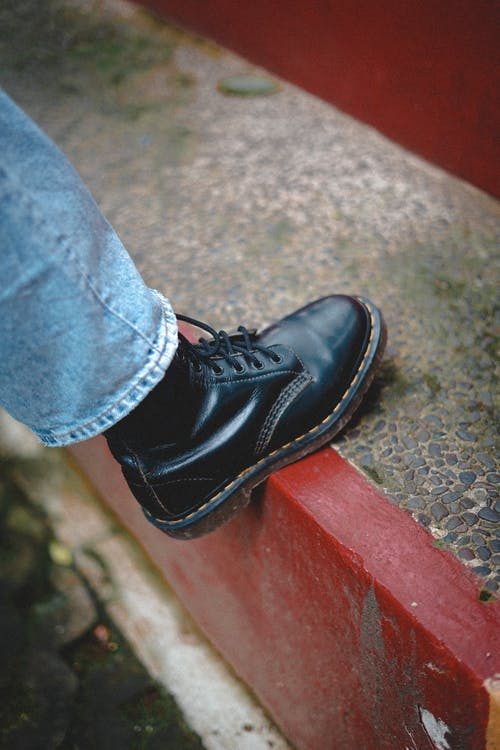 A Person in a Blue Denim Jeans and Black Leather Shoe