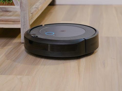 Black Round Device on Brown Wooden Flooring