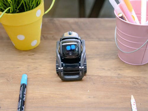 Black Miniature Robot Toy on Wooden Surface