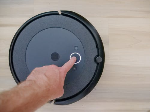 Person Pointing on Black Vacuum Cleaner