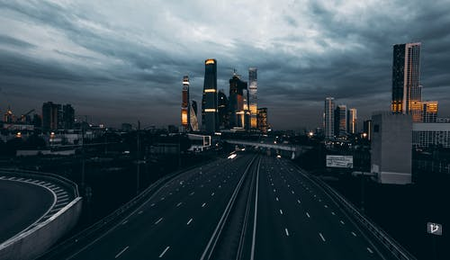 Empty Highway and City Buildings Under Gray Cloudy Sky During Night Time