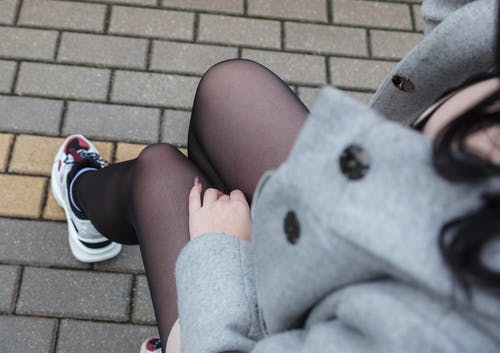 Person in Gray Coat With Black Stockings and White Rubber Shoes
