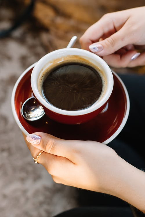 Person Holding Red Ceramic Cup With Coffee