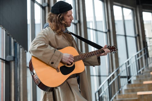 Man in Brown Coat Strumming Acoustic Guitar