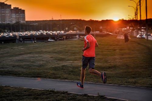 Man In Orange Shirt Jogging On Paved Pathway
