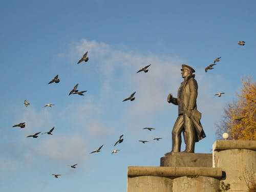 Photo of a Monument With Birds Flying Under Blue Sky
