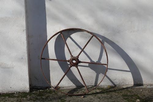 Rusty Wheel Beside White Wall