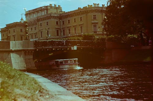 Boat Swimming Under the Bridge Beside Old Building