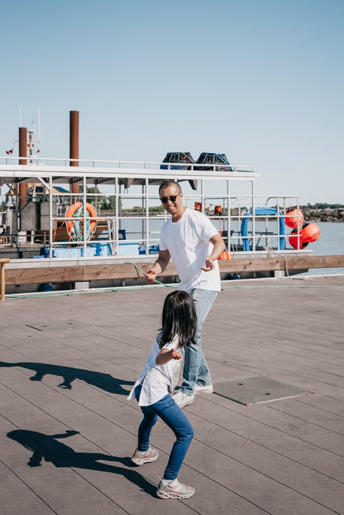 Dad and Daughter Playing Together on Wooden Dock