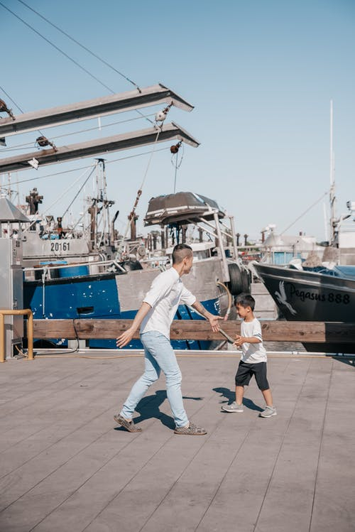 Dad and Son Playing Together on Wooden Dock