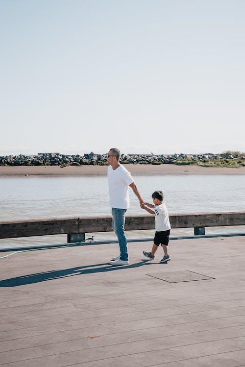 爸爸和兒子一起站在木碼頭上