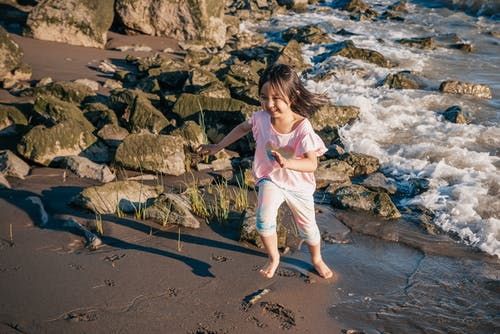 Young Girl Running on a Rocky Shore