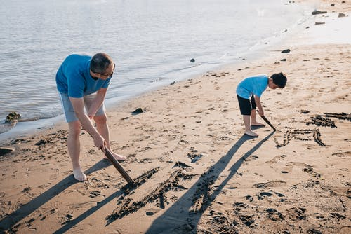 Father and Son Drawing on Sand