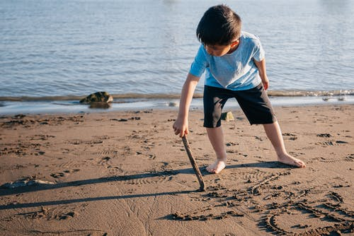 Young Boy Drawing on Sand