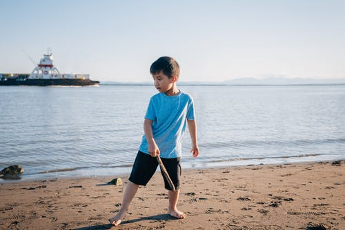 Boy in Blue Shirt Holding a Stick at the Beach