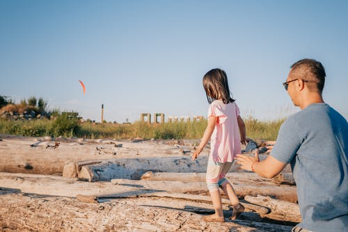 Dad Helping His Daughter Walk on a Log