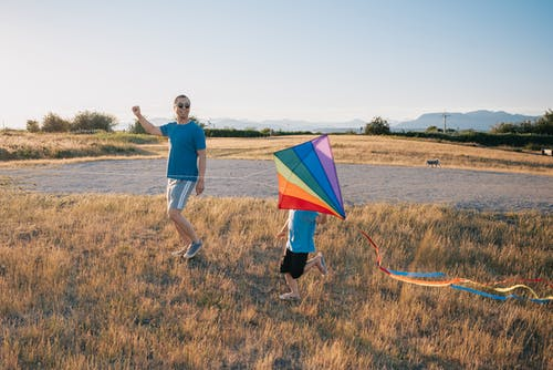 Dad and Son Having Fun Playing with Kite in the Grass Field