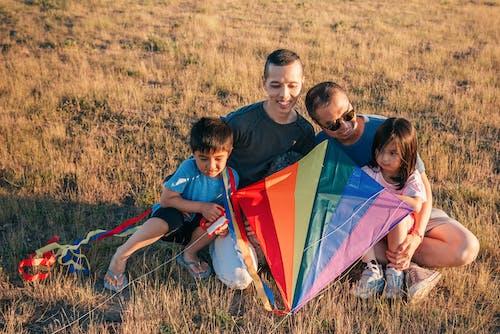 カラフルな凧を持って草の上に座って幸せな家族