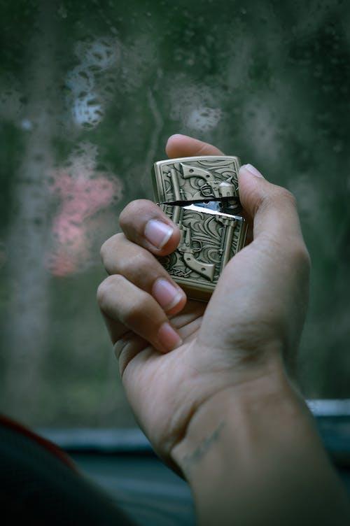 Person Holding a Cigarette Lighter
