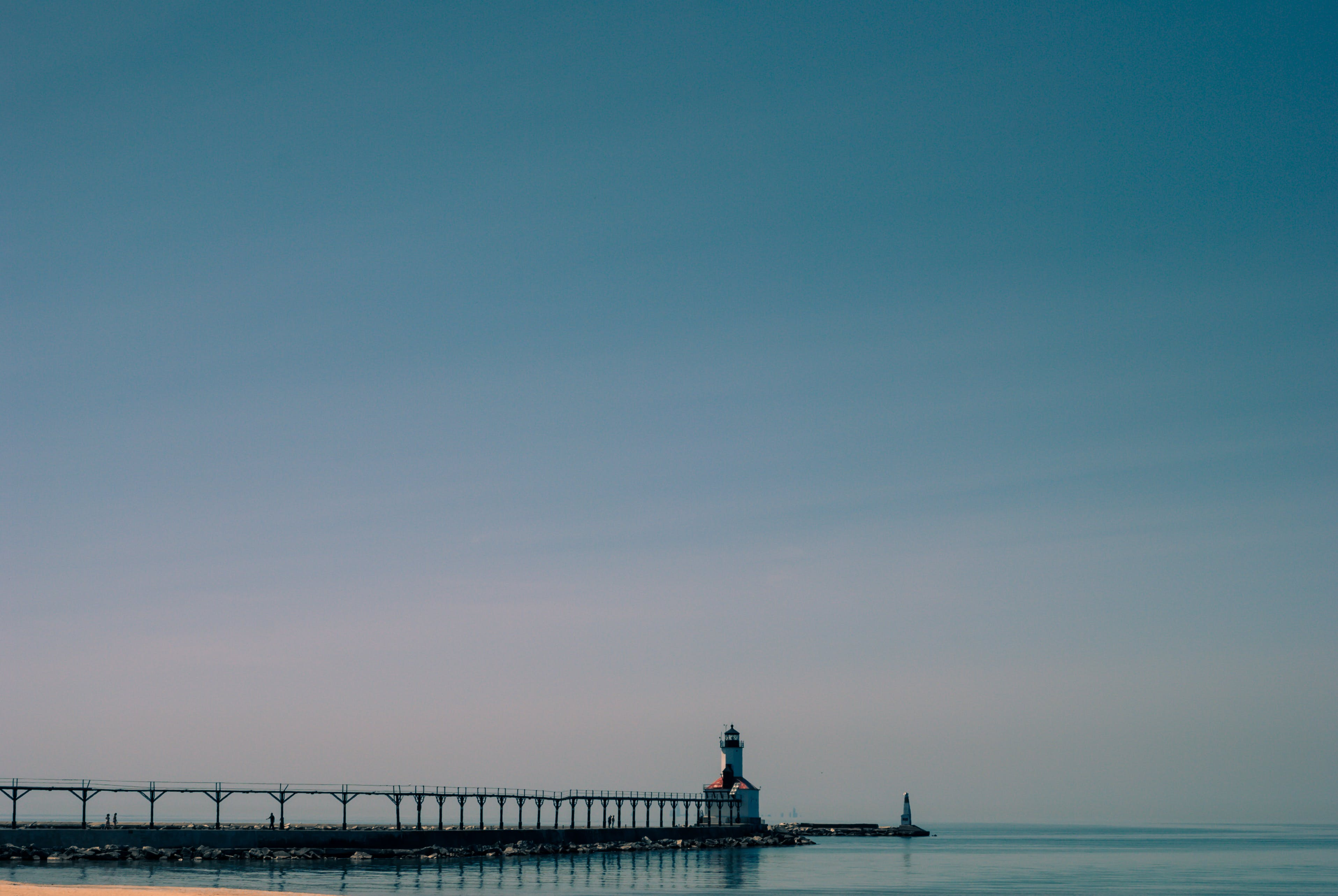 Dock Near White and Brown Concrete Lighthouse Surrounded by Calm Body of Water