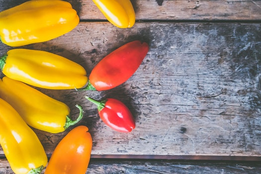 Yellow, Orange, and Red Peppers on Wooden Surface