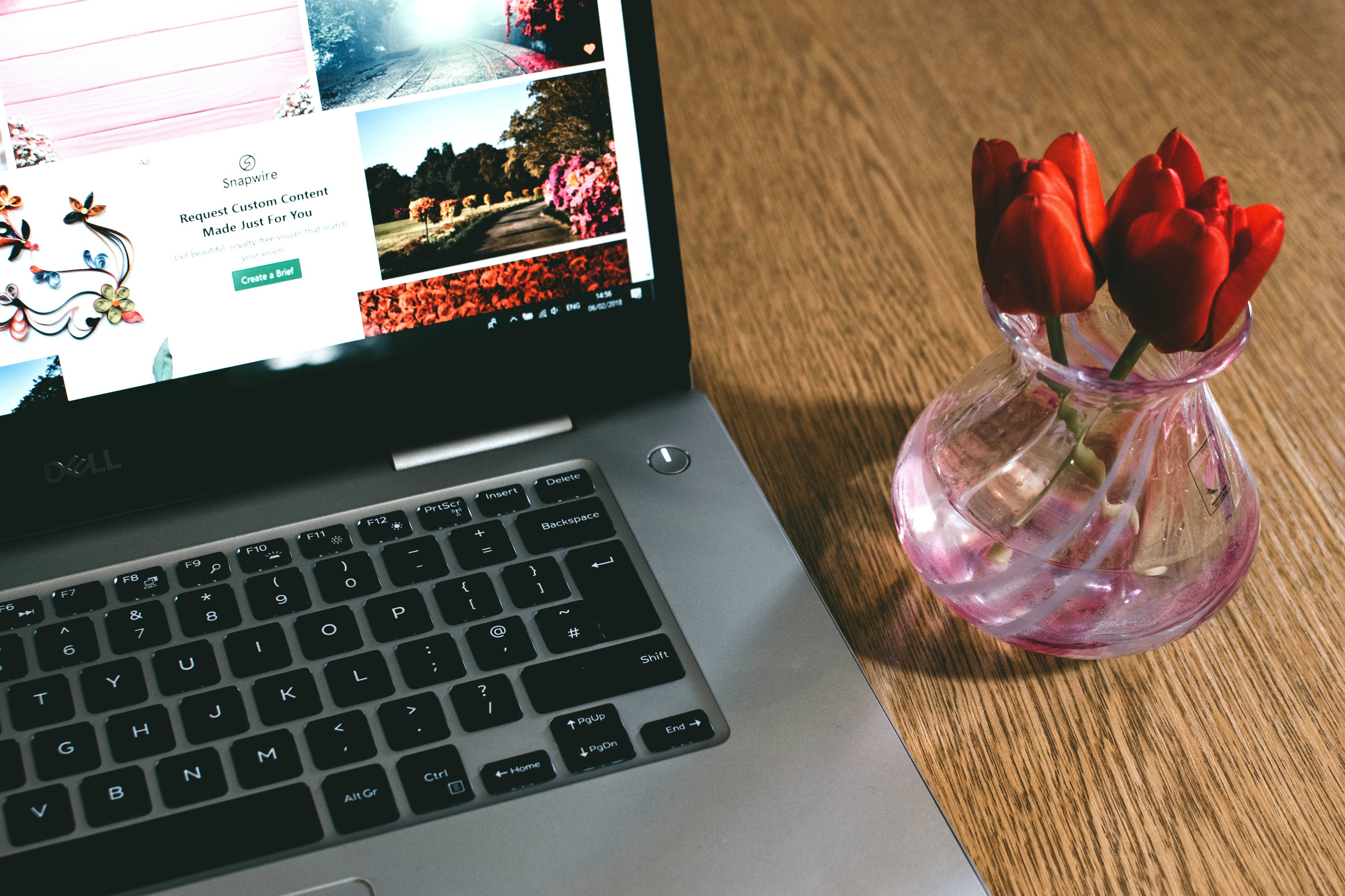 Black Dell Laptop Beside the Pink Glass Vase