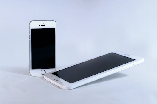 Silver Iphone 5s and White Samsung Android Smartphone