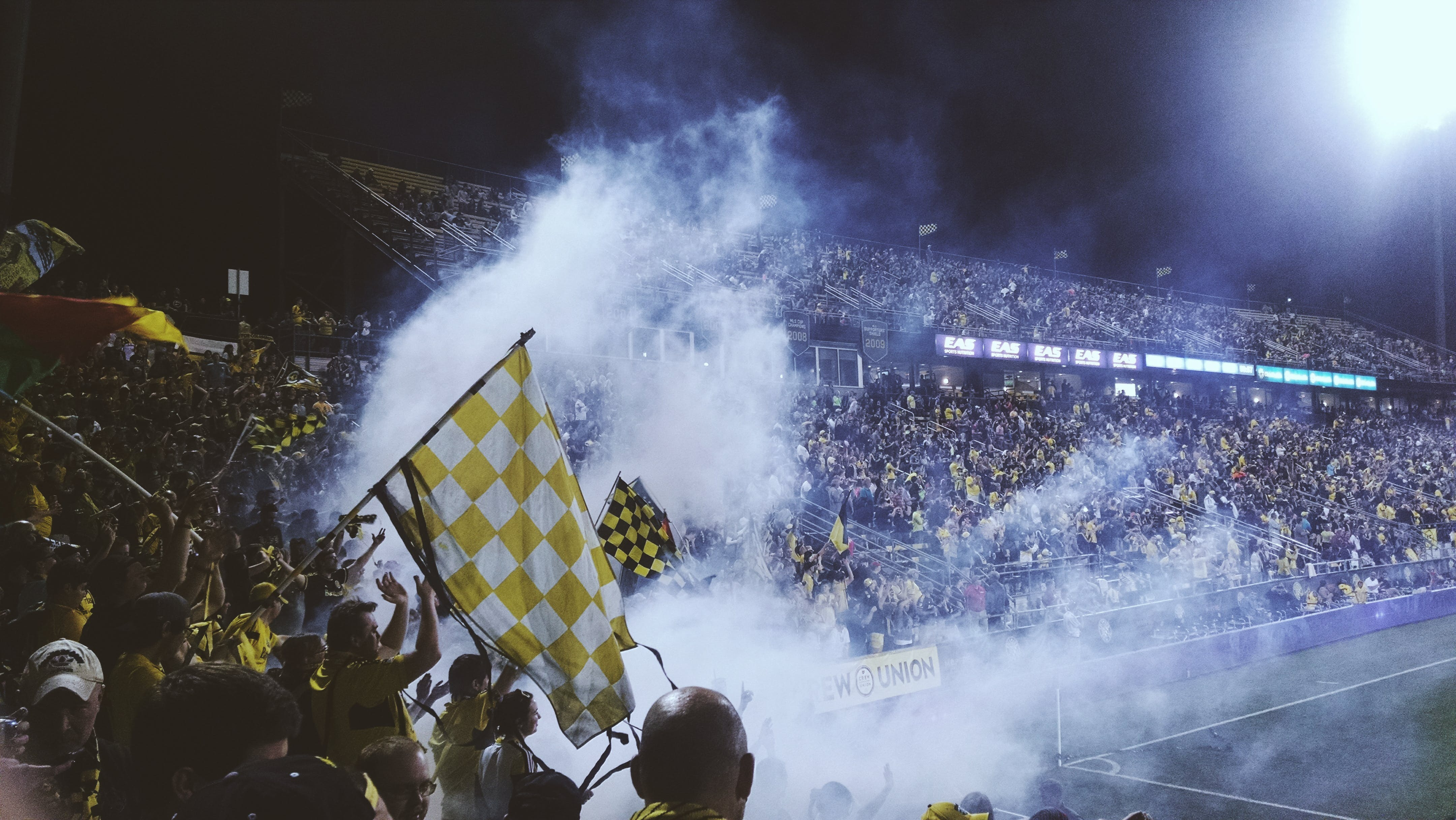 People in Stadium With Smoke at Night