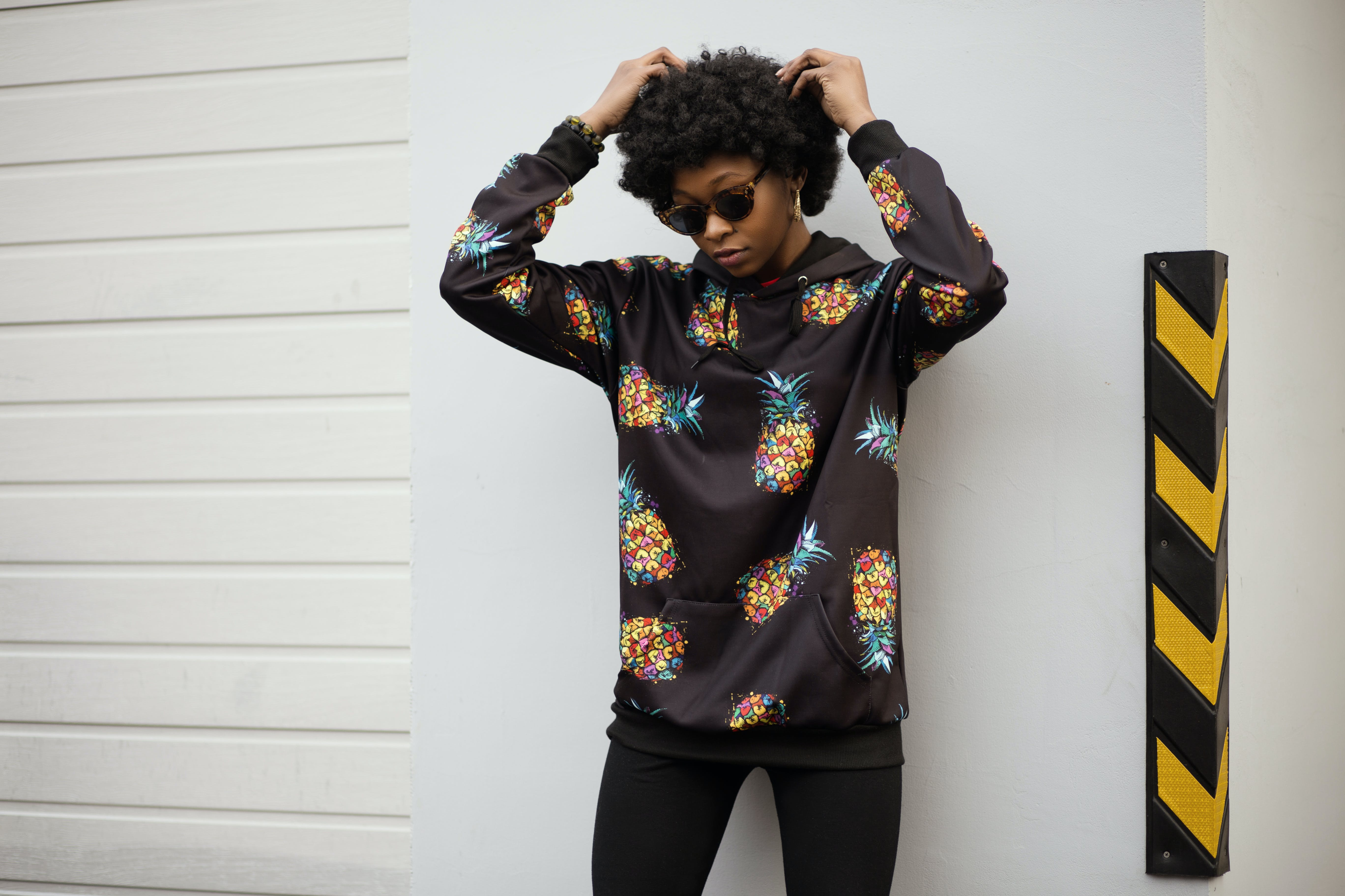 Photo of a Woman in Pineapple Print Pullover Leaning on White Wall