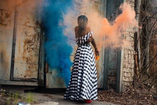 Woman Standing on Orange and Blue Smoke