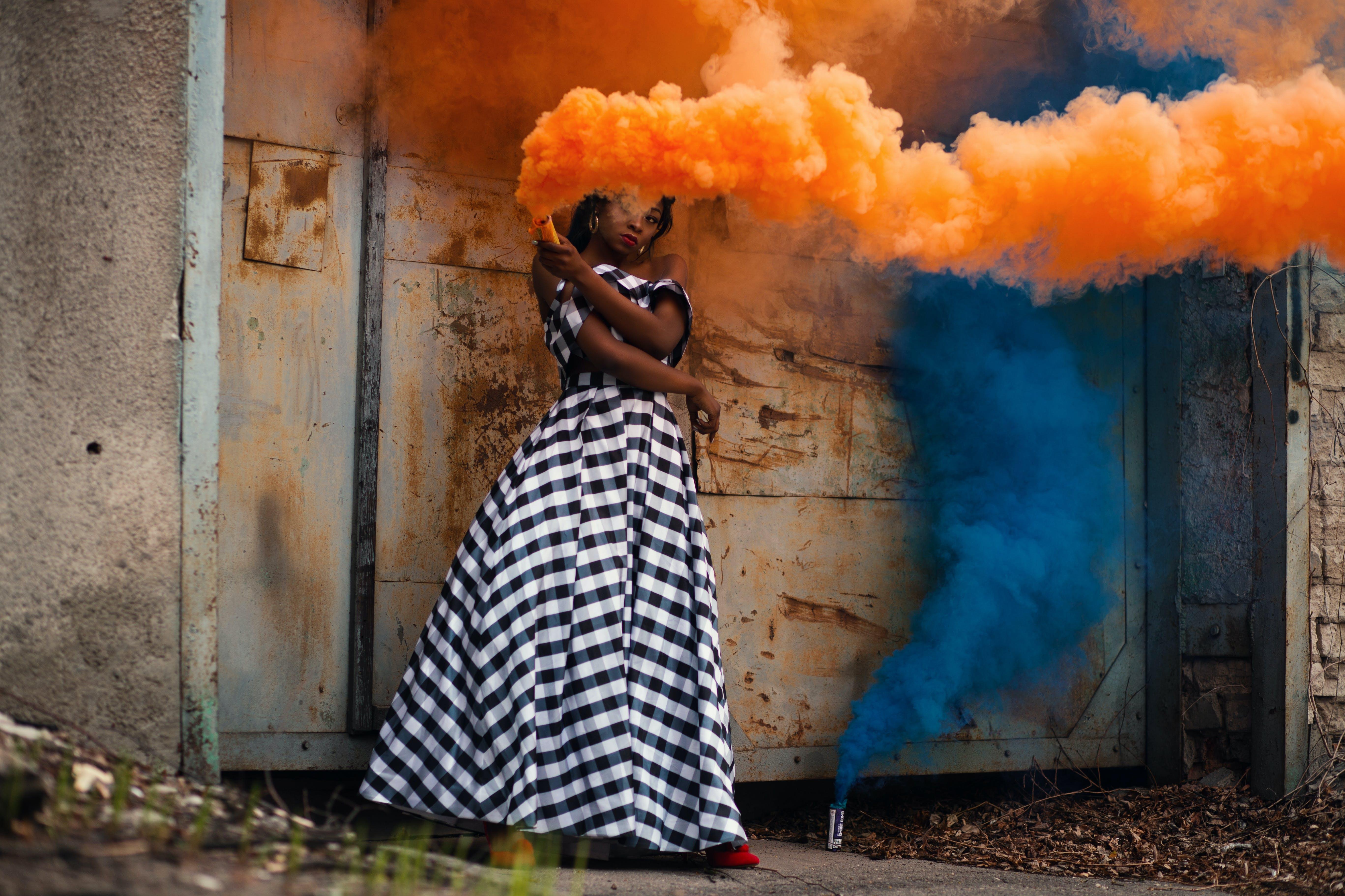 Woman in White and Black Dress Holding Orange Smoke