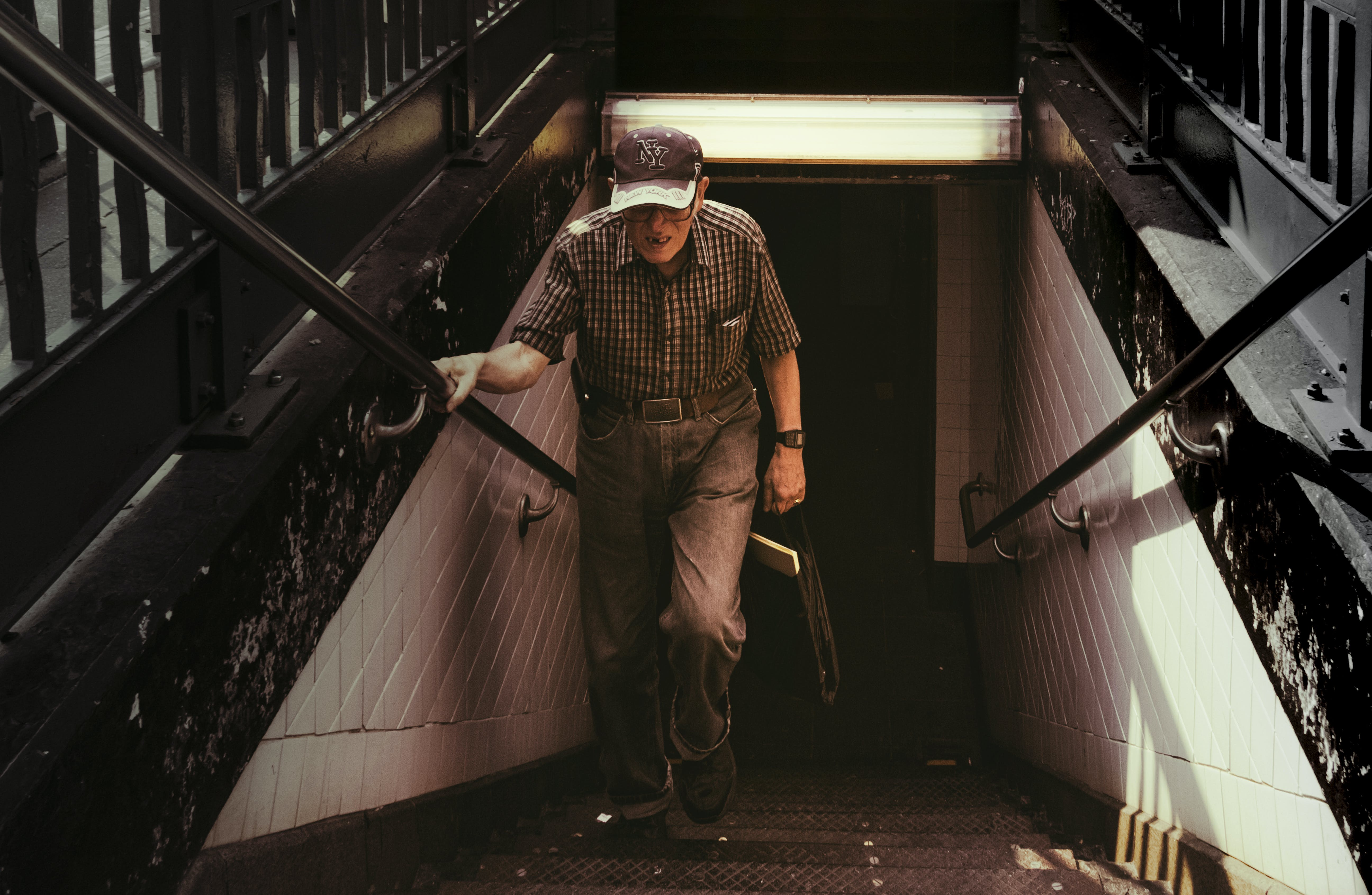 Man in Collared Shirt and Gray Pants Walking on Stairs