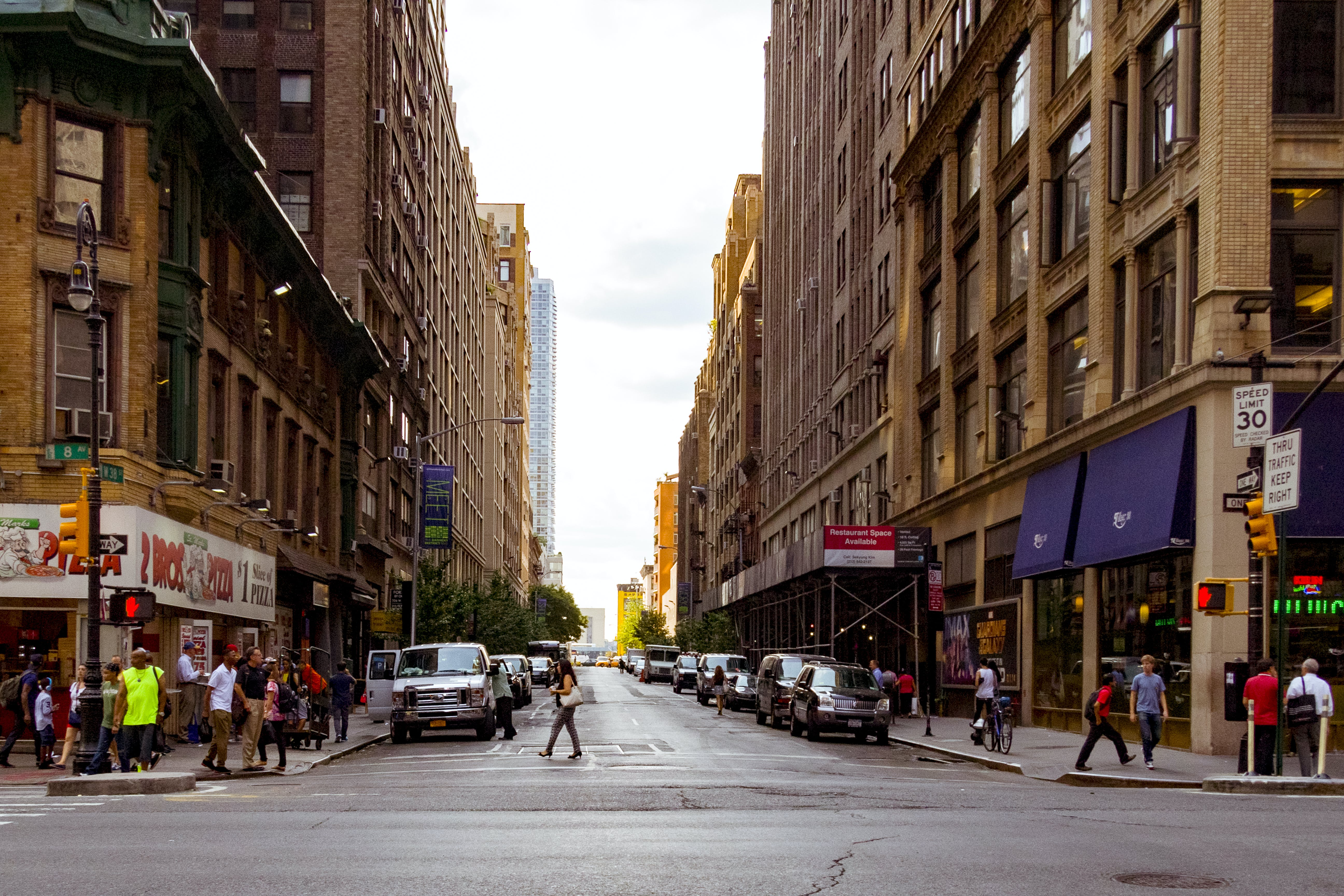 People Walking on Alley Surrounded by High Rise Buildings