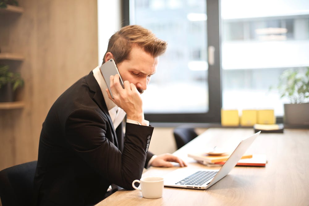 Man having a phone call in front of a laptop. | Photo: Pexels