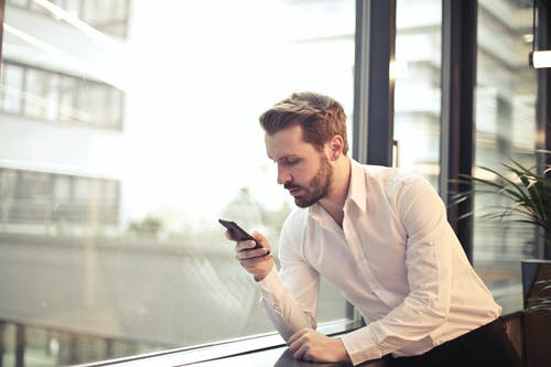 Фотография мужчины в белой рубашке с телефоном у окна