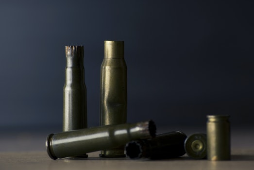 Empty Bullet Shells on Brown Surface