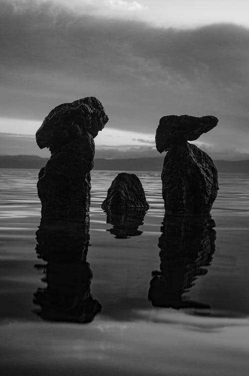Grayscale Photo of Rock Formation on Body of Water