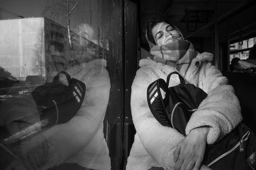 Grayscale Photo of a Person Sleeping Holding Her Backpack