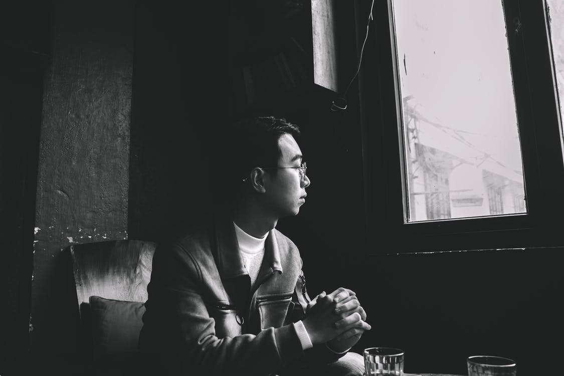Grayscale Photo of Man Sitting Near Closed Window