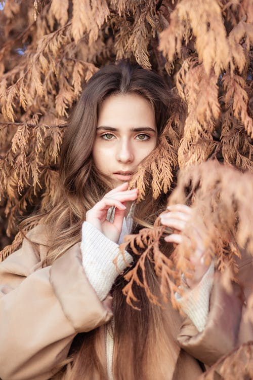 Woman in Beige Coat Surrounded by Dried Leaves