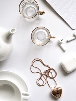 Gold-colored Heart Pendant Necklace Beside Two Glass Mugs on Table