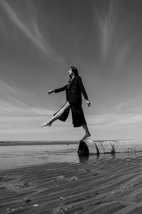 Grayscale Photo of Man in Black Jacket and Pants Jumping on Beach