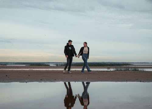 A Couple Holding Hands while Walking on a Beach