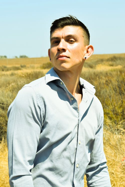 Young male in shirt and earrings looking at camera on meadow under blue sky in sunlight