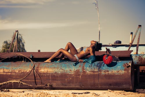 Woman in White and Blue Striped Two Piece Lying on Rustic Brown Metal Tank