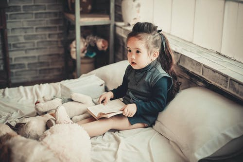 Toddler Girl Wearing Long-sleeved Top Reading Book While Sitting on Bed
