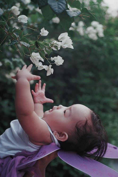 Girl in White Shirt Holding White Flowers