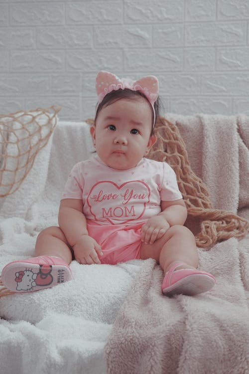 Baby in Pink Onesie Lying on Pink Textile